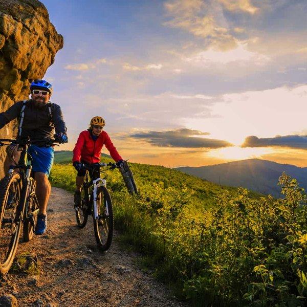 Mountain biking women and man riding on bikes at sunset mountain