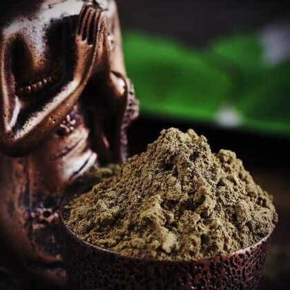 kratom powder in a bowl and with a statue on and kratom ban article