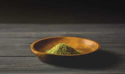 kratom powder in a bowl on table